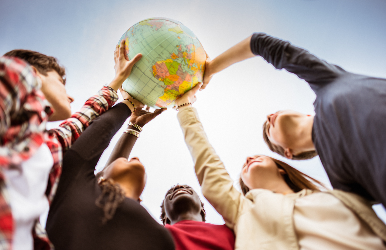 people holding up a globe together