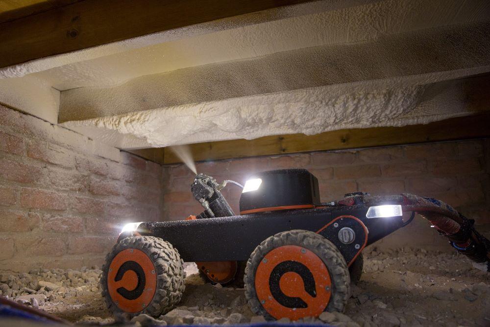 Q Bot robot spraying insulation under floorboards