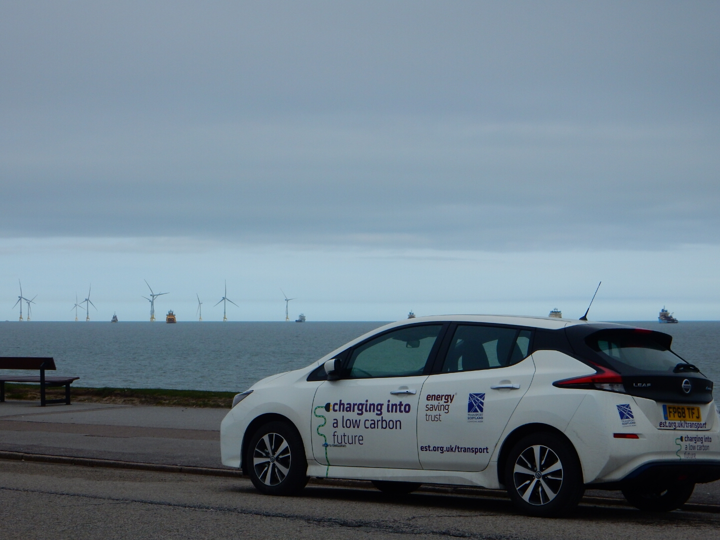 StEVie the EV on the road in Scotland, with wind turbines in the background