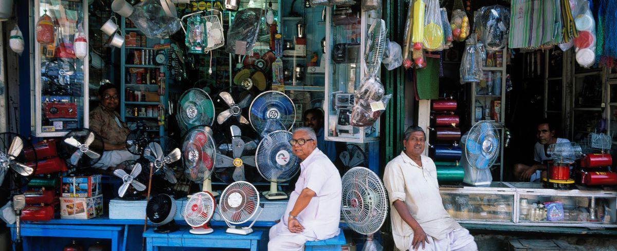 Men sitting outside a shop selling fans