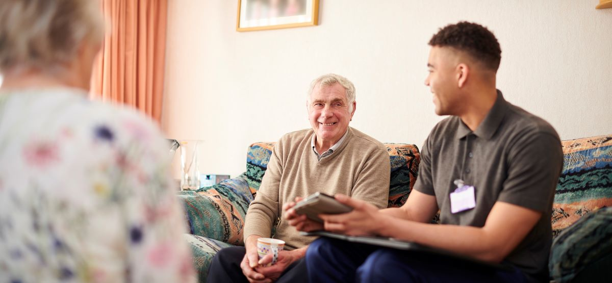 man talking to older couple in their home giving advice