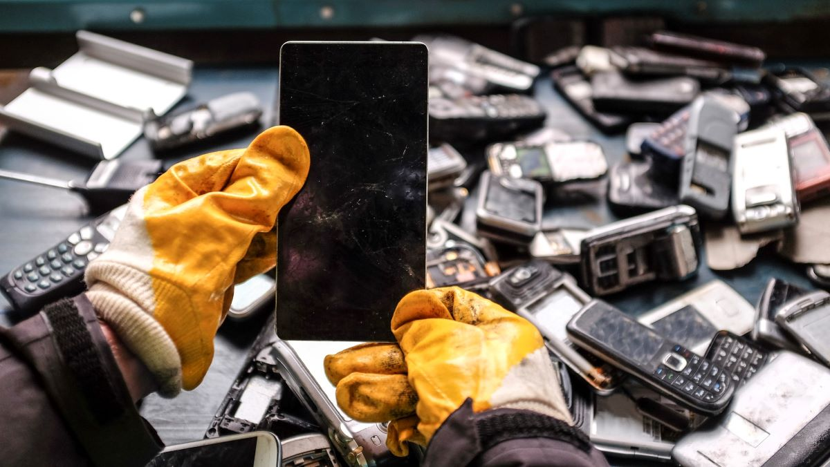 electronic waste being recycled - gloved hands hold discarded phone