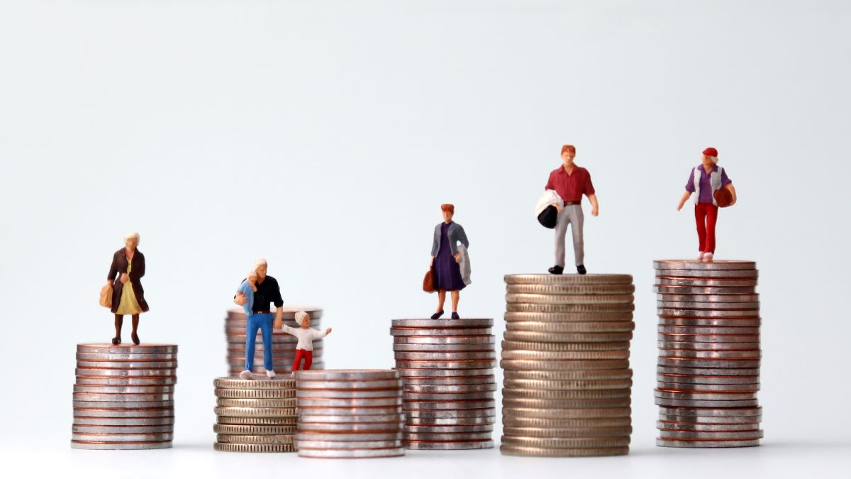 miniature people standing on top of stacks of coins of different sizes