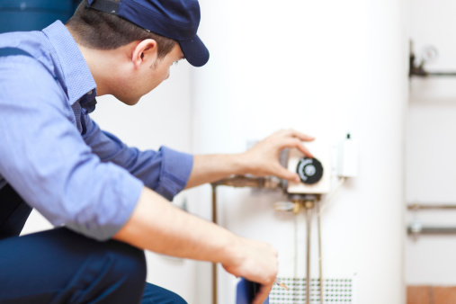 Technician adjusting boiler controls