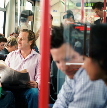full bus with man looking out the window with a newspaper