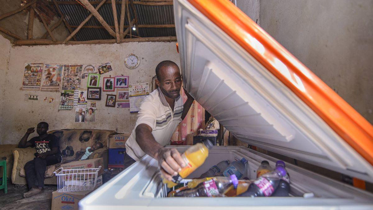 Man opening a fridge in small working area in Uganda