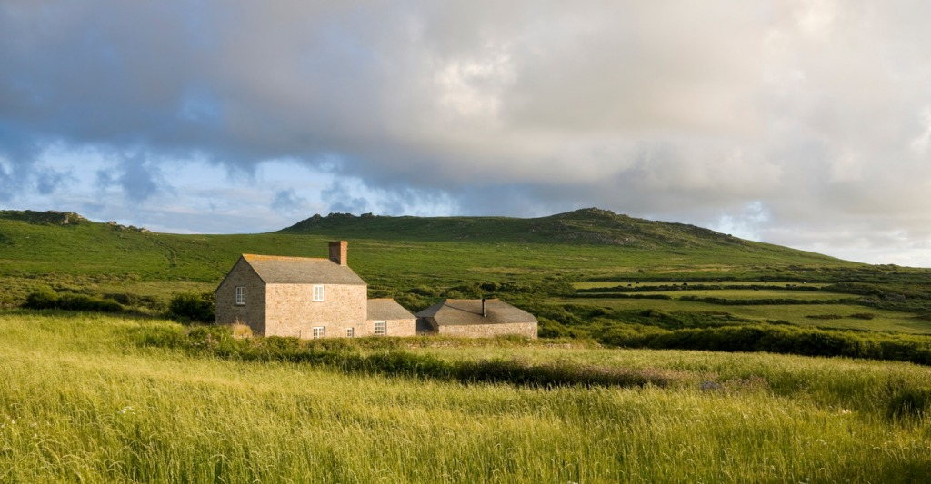 remote off-grid farmhouse in a grassy field near moorland
