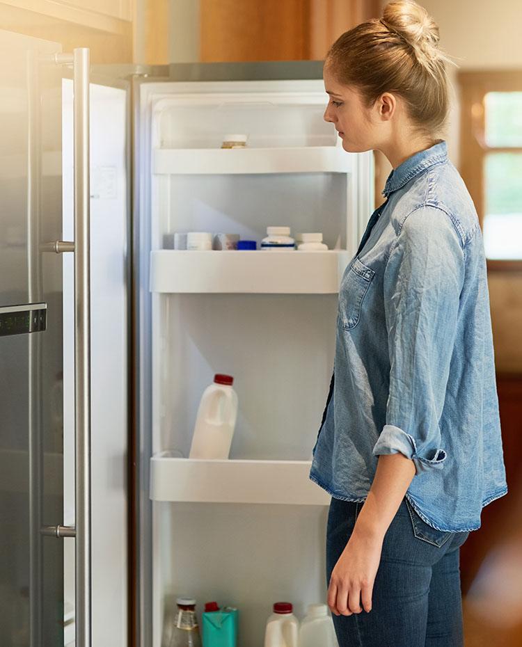 woman looking in large american style fridge