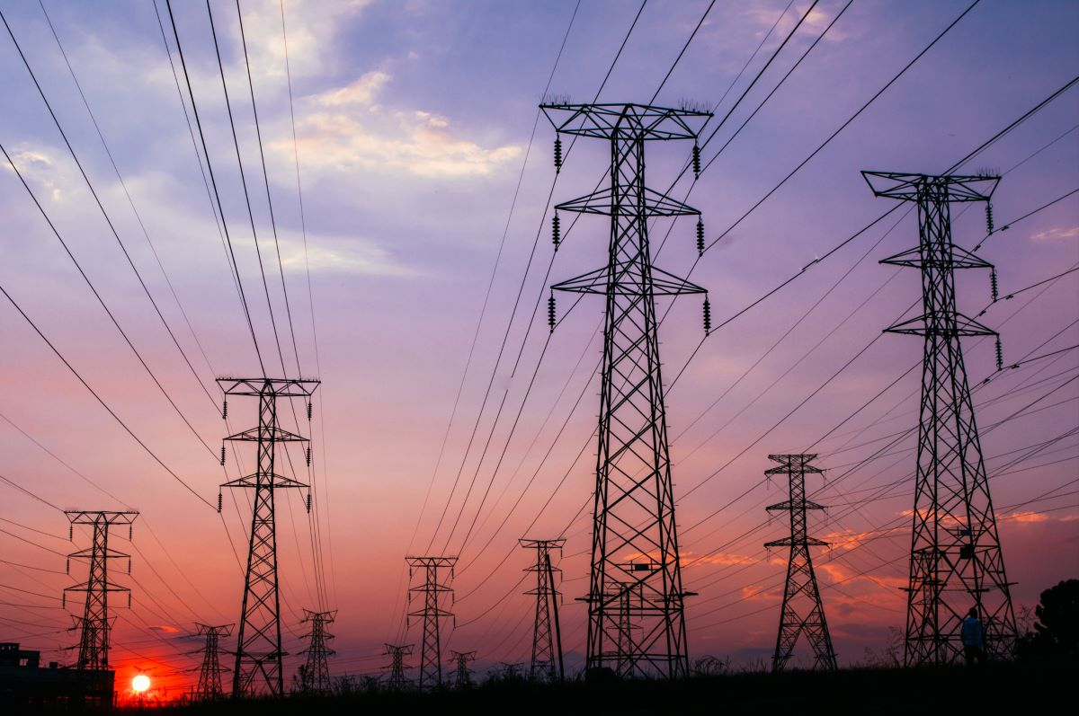 electricity pylons against sunrise