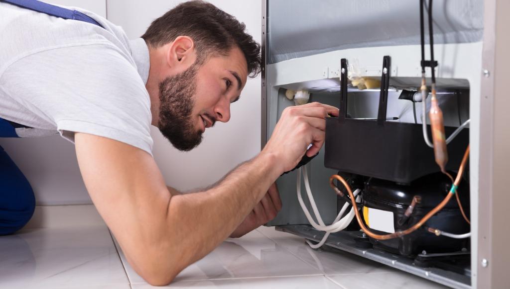 technician repairing refirigerator