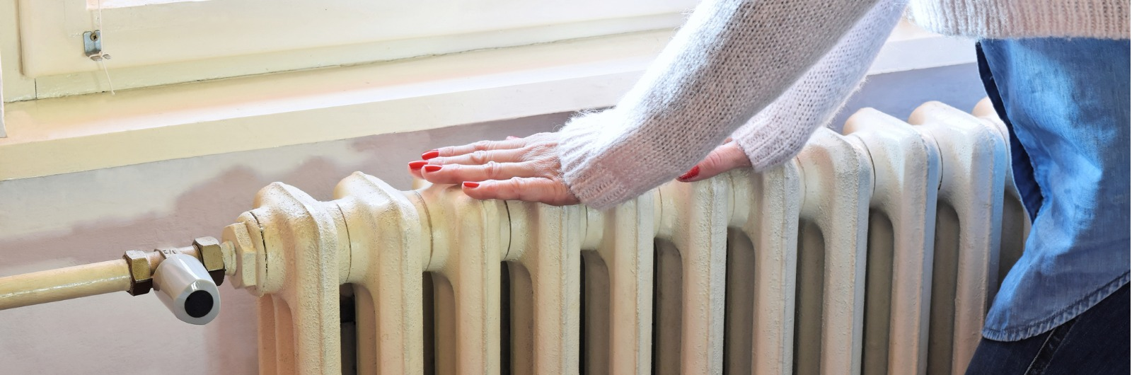 woman's hands on a radiator